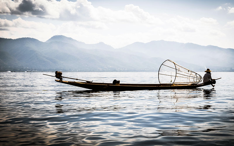 The globally renowned Inthar fisherman rowing with one leg whilst netting his fish