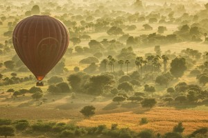 The morning mist disappearing as the balloon glides to approach the main pagodas of Bagan